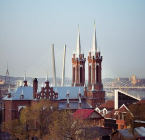 A view of Most Holy Mother of God Catholic Church in Vladivostok, showing the new roof and the steeples that were added to the building.  In the background is a section of one of the city's new cable-stayed bridges.