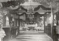 Interior of the temporary wooden church as it appeared in 1913.  Note the marble crucifix to the right of the altar.