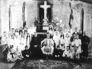 The photo donated by Zofia Brzezinska. Bishop Sliwowsky is seated next to an unknown priest. Zofia is the tall girl standing directly behind the bishop.