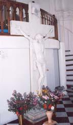 The marble crucifix at the back of the church.  Parishioners filled the vases with flowers before the Sunday Mass.